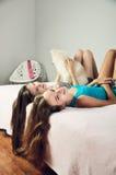 Las muchachas teñidas de la imagen dos con un Pomeranian mintieron en la cama y el laug Foto de archivo libre de regalías