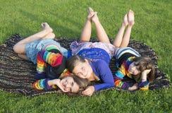 Las muchachas tienen un resto en una hierba. Foto de archivo