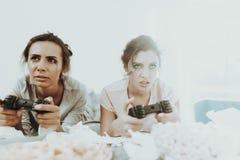 Las muchachas tristes con rimel fluido juegan la consola foto de archivo libre de regalías