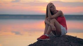 Las muchachas una se sientan cerca del lago después de entrenar, ascendente cercano metrajes