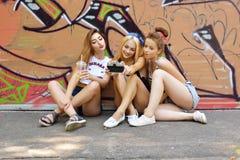 Las muchachas urbanas se divierten con la pared cercana al aire libre del grunge del vintage de la cámara retra de la foto, image Imágenes de archivo libres de regalías