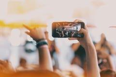 Las muchachas utilizan smartphones para tomar imágenes en los conciertos imagen de archivo