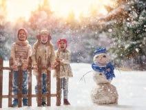 Las muchachas y el muchacho que juegan en un invierno caminan Imagenes de archivo