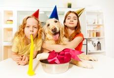 Las muchachas y el perro con el partido apoya la celebración de B-día Fotografía de archivo