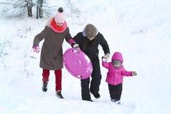 las muchachas y la madre entran adelante en la nieve que lleva a cabo las manos foto de archivo