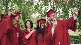 Las muchachas y los individuos de los estudiantes de graduación están tomando el selfie en birretes que llevan del día de graduac almacen de metraje de vídeo