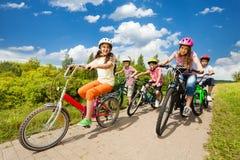 Las muchachas y los muchachos en cascos montan las bicis juntas Imagenes de archivo