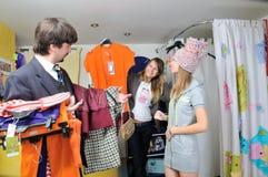 Las muchachas y un hombre compran ropa Imágenes de archivo libres de regalías