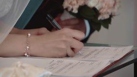 Las muestras de la novia un contrato de matrimonio, el novio se colocan próximas, primer, cámara lenta almacen de metraje de vídeo