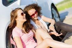 Las mujeres acercan al coche Imágenes de archivo libres de regalías
