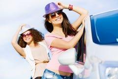 Las mujeres acercan al coche Foto de archivo