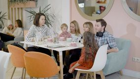 Las mujeres adultas felices, el hombre y los pequeños niños se están sentando en la tabla en el café acogedor, bebiendo el chocol almacen de metraje de vídeo