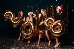 Las mujeres alegres en sombreros de la Navidad en el Año Nuevo van de fiesta Fotos de archivo