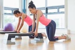 Las mujeres aptas que realizan aeróbicos del paso ejercitan en gimnasio Fotos de archivo