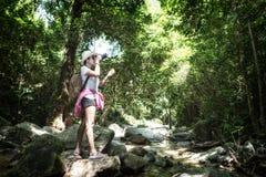 Las mujeres asiáticas del turismo del inconformista toman una foto de la cascada en bosque profundo imagen de archivo libre de regalías