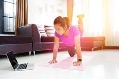 Las mujeres asiáticas ejercitan haciendo el arqueamiento detrás enderezando la pierna encima del entrenamiento en casa foto de archivo