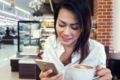 Las mujeres asiáticas están dobladas para mirar el teléfono y la consumición Foto de archivo libre de regalías
