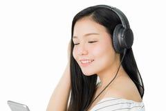 Las mujeres asiáticas están escuchando la música de los auriculares negros En un humor cómodo y bueno foto de archivo