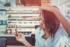 Las mujeres asiáticas están mirando fijamente su teléfono celular Imagen de archivo libre de regalías
