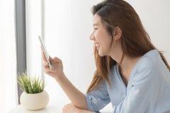 Las mujeres asiáticas están sonriendo usando smartphone en casa Imagen de archivo