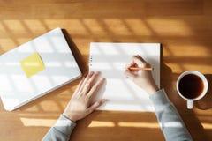 Las mujeres asiáticas están tomando notas sobre la tabla de madera con las tazas de café y los ordenadores portátiles en casa foto de archivo