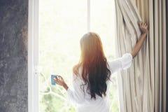 Las mujeres asiáticas que beben el café y despiertan en su cama descansada completamente imagen de archivo libre de regalías