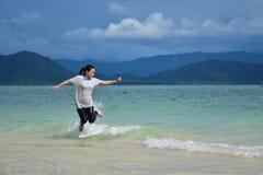 Las mujeres asiáticas saltan sobre la onda Imagen de archivo libre de regalías
