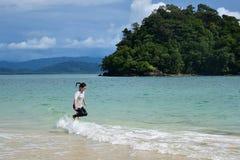 Las mujeres asiáticas saltan sobre la onda del mar Fotos de archivo