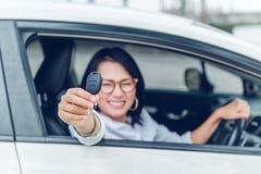 Las mujeres asiáticas son muy felices Después de que ella consiguiera el foco del coche en la k Fotos de archivo