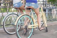 Las mujeres atractivas hermosas se vistieron en pantalones cortos cortos viajan en bicicleta Foto de archivo libre de regalías