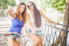 Las mujeres atractivas hermosas se vistieron en pantalones cortos viajan en bicicleta Imagen de archivo libre de regalías