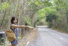 Las mujeres aumentan su coche que agita del brazo en el camino con la cubierta del árbol imagenes de archivo