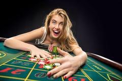 Las mujeres bonitas jovenes que juegan la ruleta ganan en el casino Fotografía de archivo libre de regalías
