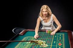 Las mujeres bonitas jovenes que juegan la ruleta ganan en el casino Imagenes de archivo