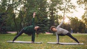 Las mujeres bonitas son deportes de moda que la ropa está entrenando al aire libre a hacer yoga que disfrutan del movimiento, air metrajes