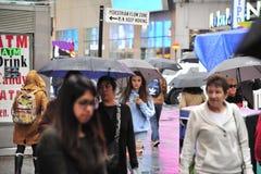 Las mujeres caminan a través de la ciudad en la lluvia Imagen de archivo