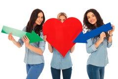 Las mujeres casuales están señalando sus flechas a su corazón Fotografía de archivo
