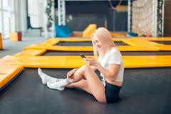 Las mujeres caucásicas juegan con su teléfono elegante en trampolín Fotos de archivo