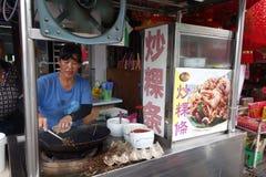 Las mujeres cocinan los tallarines kway del teow en el mercado de la noche de la comida de la calle adentro fotos de archivo