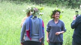Las mujeres con las coronas de la flor presentan delante de smartphone Día de pleno verano anual almacen de video