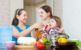 Las mujeres con el niño cocinan con las verduras en cocina Foto de archivo