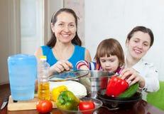 Las mujeres con el niño cocinan verduras en la cocina Fotos de archivo libres de regalías