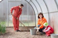 Las mujeres con el niño trabajan en el invernáculo imagen de archivo