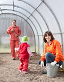 Las mujeres con el niño trabajan en el invernáculo Fotos de archivo libres de regalías