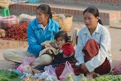 Las mujeres con el niño venden verduras en el mercado de la comida en Luang Prabang, Laos fotos de archivo