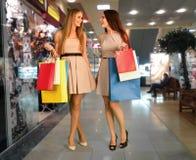 Las mujeres con los panieres están haciendo la compra en la tienda Imágenes de archivo libres de regalías