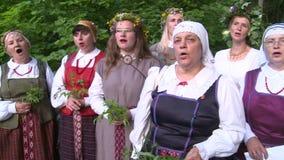 Las mujeres con ropa popular nacional firman sostener las flores Día de Saint John del pleno verano metrajes
