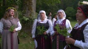 Las mujeres con ropa popular nacional firman sostener las flores almacen de video