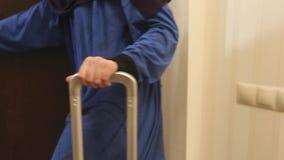 Las mujeres con una manija de la maleta salen del cuarto, concepto de turismo, salida, tarifas para el viaje almacen de video