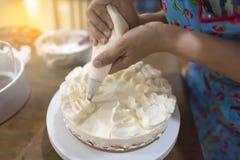 Las mujeres dan el adornamiento con un bolso de los pasteles con crema Foto de archivo
